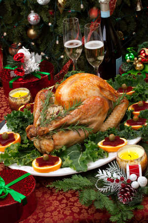 roast turkey: Christmas-decorated table with feast, gifts, roasted turkey, candles, champagne, and Christmas tree on back