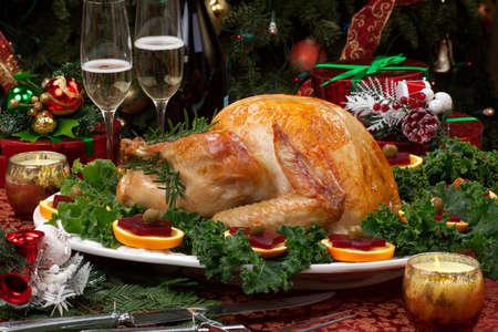 cena navideña: Navidad decorada mesa con fiestas, regalos, pavo asado, velas, champagne, y el árbol de Navidad en la espalda Foto de archivo