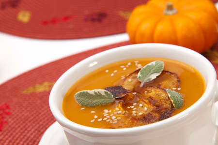 sage: Closeup of a cup of hot delicious spicy roasted pumpkin soup with pumpkin crisps, sage and sesame seads  Stock Photo