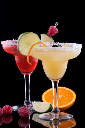 Orange and Raspberry margaritas in chilled glass over black background on reflection surface