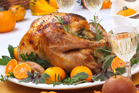 thanksgiving turkey: Garnished citrus glazed roasted turkey on holiday table, pumpkins, flowers, and white wine