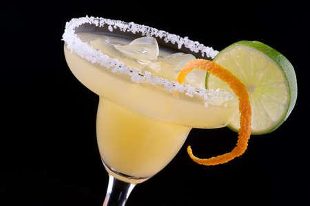 Orange Margarita in gekühltes Glas über schwarzem Hintergrund auf Reflexion Oberfläche, mit frischen Limette und Orange Die beliebtesten Cocktails Serie garniert Standard-Bild