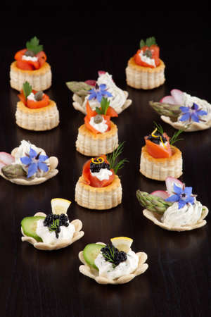 Assorted mini canapes of black caviar on Creme Fraiche, smoked salmon, and  cheese and fresh garden vegetables over black background Stock Photo - 14971826