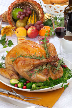 thanksgiving: Garnished roasted turkey on fall festival decorated table with horn of plenty and red wine Stock Photo