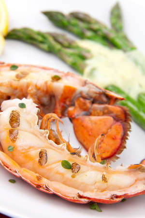 Closeup of delicious grilled lobster tails served with asparagus and bearnaise sauce photo