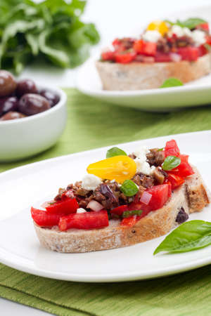 Closeup of delicious olive tapenade tomato Bruschetta with feta cheese and fresh basil leaves  photo