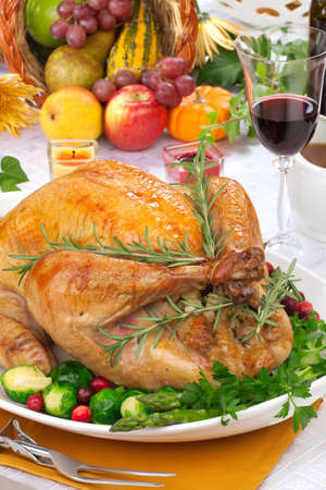thanksgiving dinner: Garnished roasted turkey on fall festival decorated table with horn of plenty and red wine Stock Photo