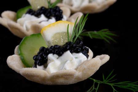 Closeup of black caviar on Creme Fraiche over black background  版權商用圖片