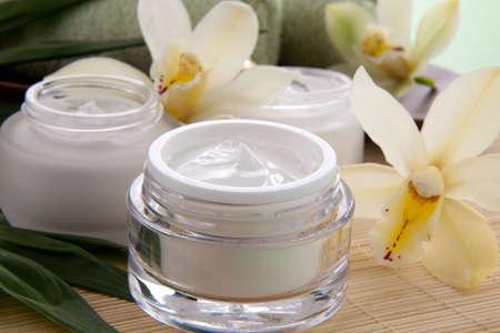 cremas faciales: Cymbidium orquídea blanca flor y tarro de crema hidratante cara para el tratamiento de spa