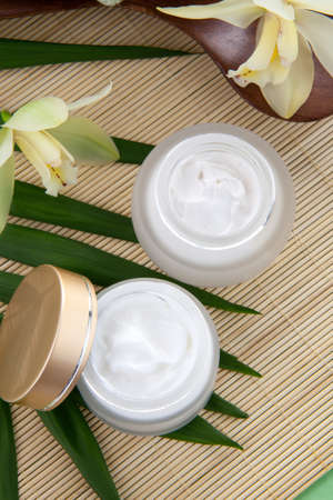 cremas faciales: Blanco orquídea Cymbidium flores y tarro de crema hidratante cara para el tratamiento de spa