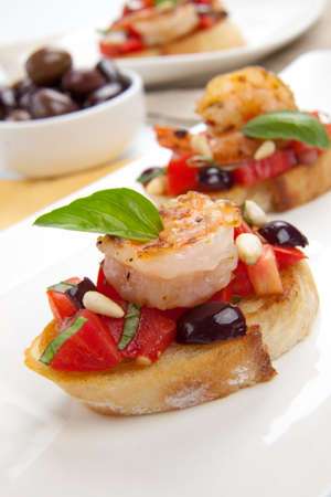 pine nuts: Closeup of delicious Olive - Tomato Bruschetta with garlic shrimp and pine nuts  Stock Photo