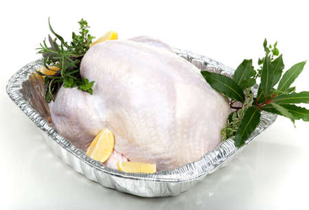 Closeup of raw uncooked turkey in roasting dish garnished with lemons, and aromatic herbs  photo
