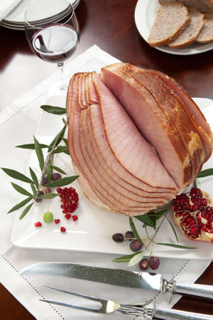 Closeup of plate with ham , bread and olives on dinning table set with glazed whole baked sliced ham, garnished with pomegranate