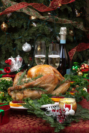 Christmas-decorated table with feast, gifts, roasted turkey, candles, champagne, and Christmas tree on back