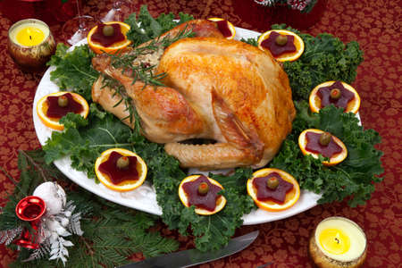 Tisch mit Fest, Geschenke, gebratenen Truthahn, Kerzen, Champagner und Weihnachtsbaum auf dem Rücken Weihnachten dekoriert Standard-Bild