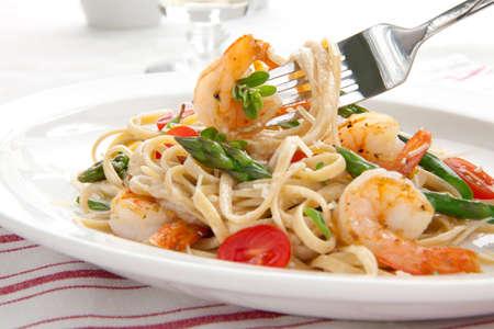 Gesunde Vollkorn Linguine mit Garnelen, Spargel, Kirschtomaten, frischem Parmesan und Oregano Standard-Bild