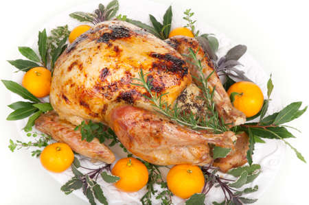 Garnished citrus glazed roasted turkey on tray over white background photo