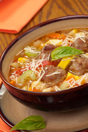 Closeup of bowl of hot fresh Italian Meatball Soup and wholegrain bread photo