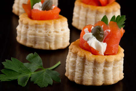 canapes: Closeup of smoked salmon canape with capers and parsley over black background  Stock Photo