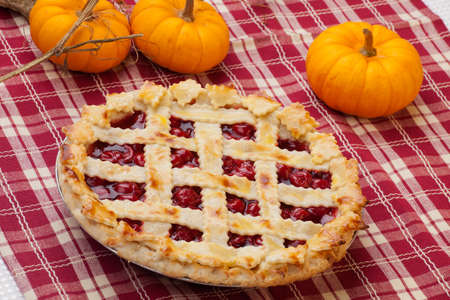 Cherry pie with lattice top on fall themed napkin, and mini pumpkins  photo