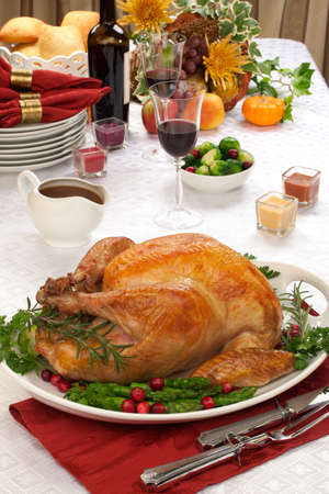 Garnished roasted turkey on fall festival decorated table with horn of plenty and red wine Stock Photo - 16049899