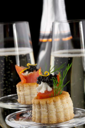 Closeup of black caviar on Creme Fraiche and smoked salmon canape and flutes of Champagne over black background