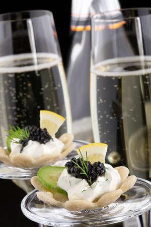 Close-up van zwarte kaviaar op Room Fraiche en fluiten champagne op zwarte achtergrond