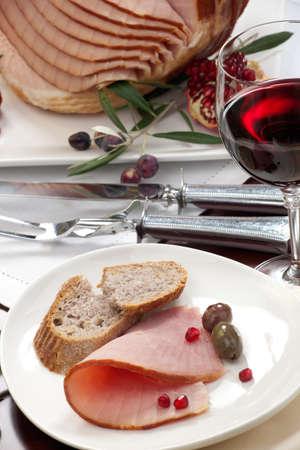 pan y vino: Primer plano de la placa con jamón, pan y aceitunas en la mesa de comedor conjunto con toda vidriada jamón cocido en rodajas, adornado con granada