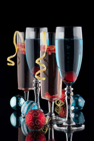 chilled: Closeup of flutes of blue champagne and pomegranate champagne cocktails, and Christmas ornaments on black background