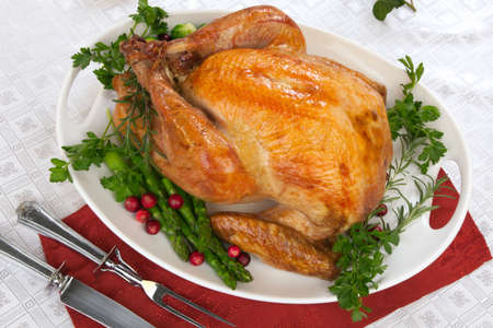 garnished: Garnished roasted turkey on fall festival decorated table with horn of plenty and red wine Stock Photo