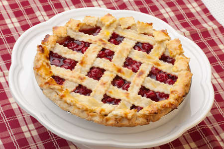 Cherry pie with lattice top on fall themed napkin, and mini pumpkins