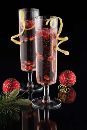Closeup of glasses of pomegranate champagne cocktail, garnished with lemon twist, and Christmas ornaments on black background