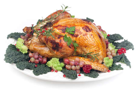 Glazed roasted turkey garnished with grapes, pomegranates, and broccoli over white background photo