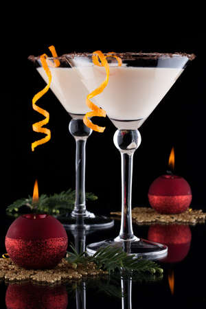 Closeup of Orange Chocolate Dream - festive Christmas cocktail with candles and ornamets over black background  Orange twist and chocolate rim  Holiday cocktails series  Stock Photo