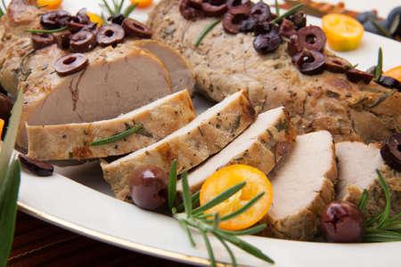 verm�: Primer plano de rodajas de lomo delicioso asado de cerdo con aceitunas, vermut y c�tricos