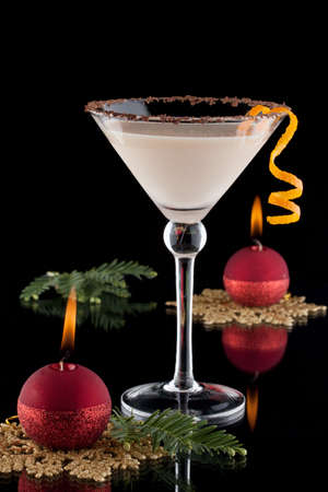baileys: Closeup of Orange Chocolate Dream - festive Christmas cocktail with candles and ornamets over black background  Orange twist and chocolate rim  Holiday cocktails series  Stock Photo