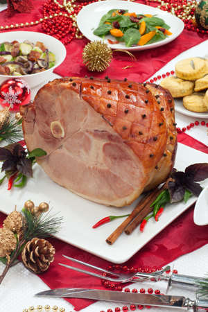 Roasted spiced ham on holiday dinning table, garnished with cloves, cinnamon sticks, hot chili pepper, and purple basil  Side dishes and Christmas ornaments around