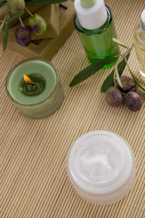Fancy face cream  with olive soap bars, olive oil, and scented candles for spa treatment photo