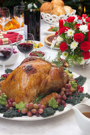 Holiday-decorated table, Christmas tree, champagne, and roasted turkey  Stock Photo - 16696920