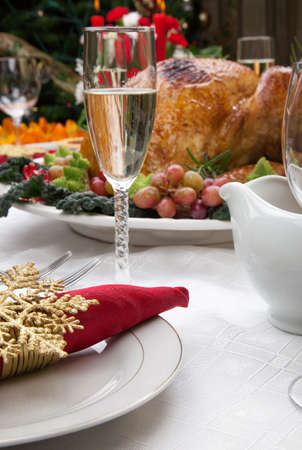 Holiday-decorated table, Christmas tree, champagne, and roasted turkey