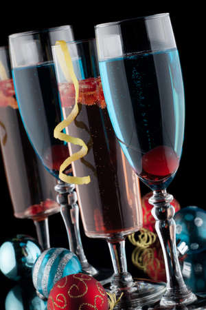Closeup of flutes of blue champagne and pomegranate champagne cocktails, and Christmas ornaments on black background