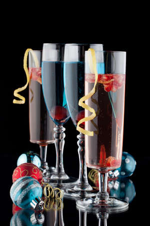 closeup of flutes of blue champagne and pomegranate champagne cocktails and christmas ornaments on black