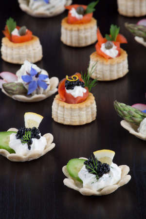 Assorted mini canapes of black caviar on Creme Fraiche, smoked salmon, and  cheese and fresh garden vegetables over black background.