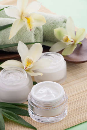 cremas faciales: Cymbidium orquídea blanca flor y tarro de crema hidratante cara para el tratamiento de spa.