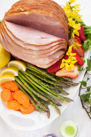 Festive glazed ham for Easter celebration dinner garnished with asparagus, carrots, strawberry, and lemon wedges