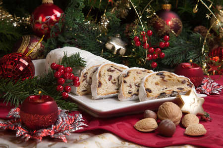 Traditional German Christmas cake - Cranberry Stollen, Christmas tree, ornaments, and candles