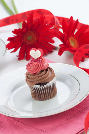 Closeup of chocolate cupcake on Valentine day with heart shaped decoration  Tea and scarlet gerberas  photo
