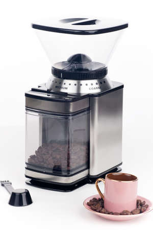 Closeup of modern coffee grinder with coffee beans around over white Stock Photo - 17245740