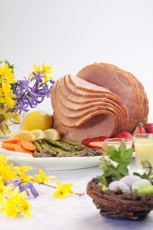Festive glazed ham for Easter celebration dinner garnished with asparagus, carrots, strawberry, and lemon wedges