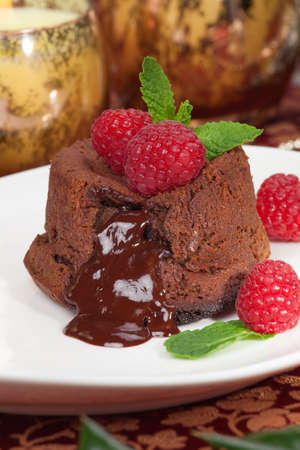Delicious dark chocolate lava cake dessert served with fresh raspberries and mint  Surrounded by Christmas ornaments  Stockfoto